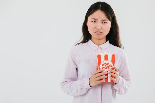 Donna confusa con un sacco di popcorn Foto Gratuite