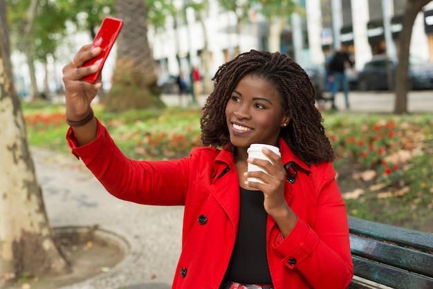 Donna contenta che prende selfie con lo smartphone sulla via Foto Gratuite