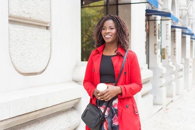 Donna contenta con caffè per andare a camminare sulla strada Foto Gratuite