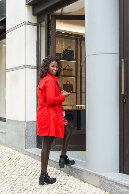 Donna contenta con il negozio entrante dello smartphone Foto Gratuite