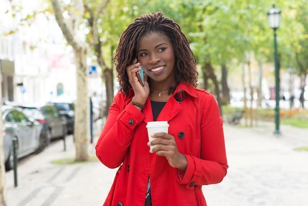 Donna contenta con la tazza di carta che parla dallo smartphone Foto Gratuite