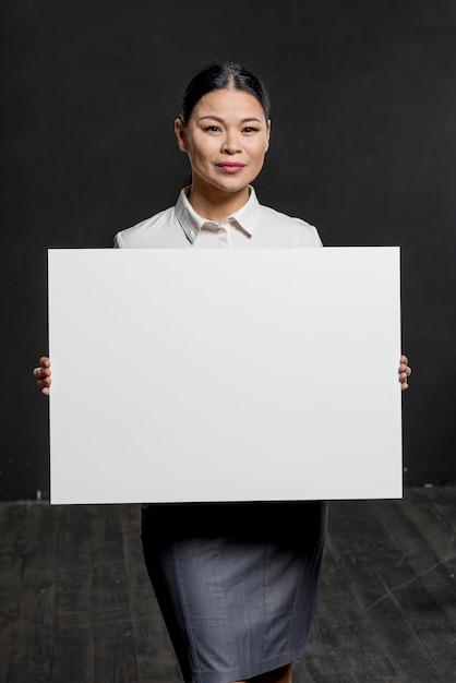 Donna convenzionale che tiene foglio di carta bianco Foto Gratuite