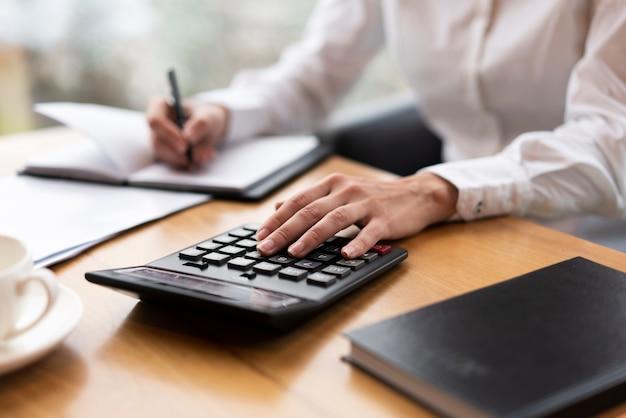 Donna d'affari calcolando e scrivendo Foto Gratuite