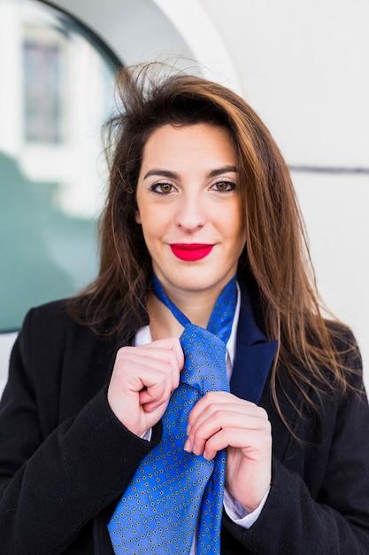 Donna d'affari che annoda cravatta blu Foto Gratuite