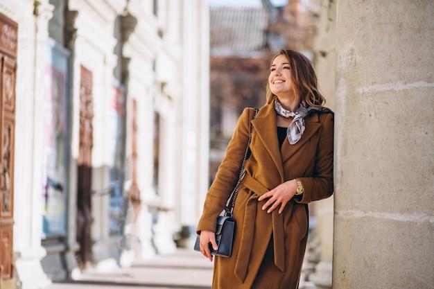 Donna d'affari felice in cappotto in strada Foto Gratuite