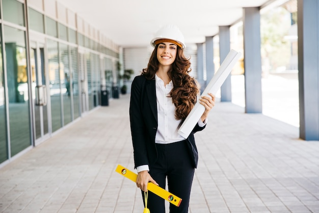 Donna d'affari sorridente con piano e livello Foto Gratuite