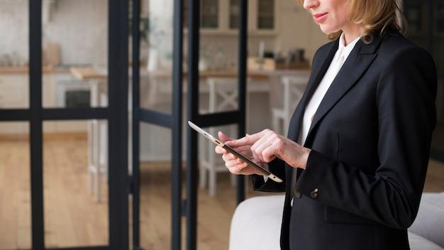 Donna d'affari utilizzando la tavoletta Foto Gratuite