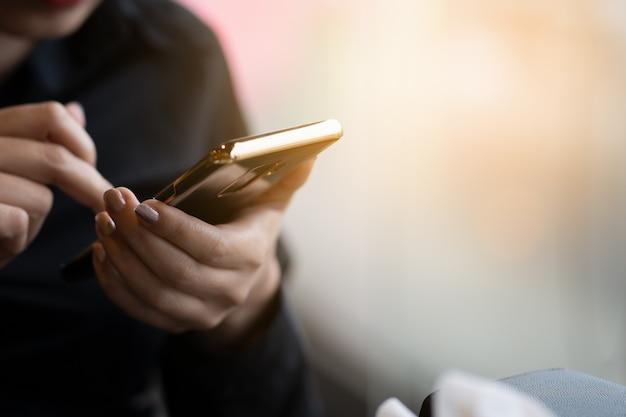 Donna d'affari utilizzando smart phone per inviare messaggi o e-mail Foto Premium