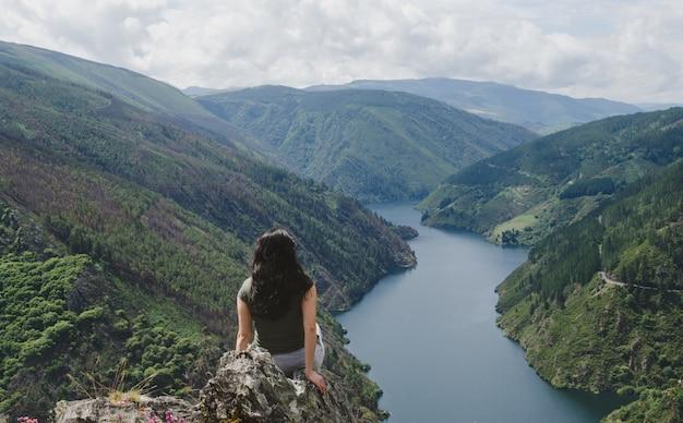 Donna da dietro guardando il fiume. Foto Premium