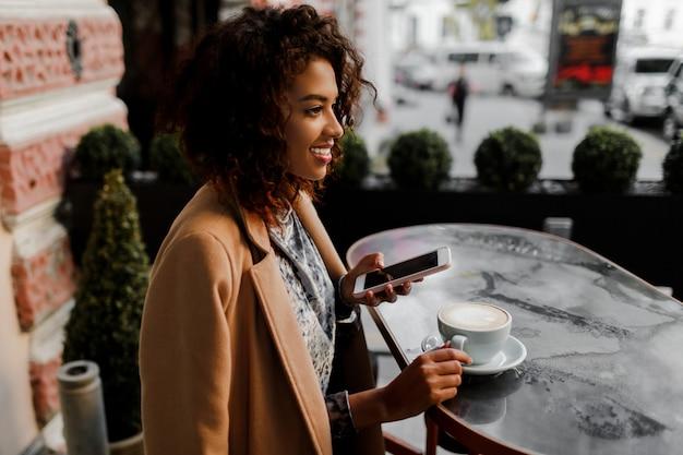 Donna dalla pelle scura con acconciatura afro che controlla i suoi feed di notizie o messaggi tramite i social network Foto Gratuite