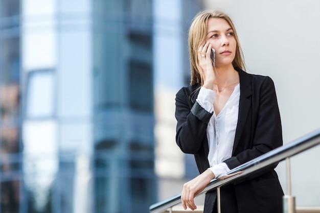 Donna del colpo medio che distoglie lo sguardo di fronte ad un bulding Foto Gratuite