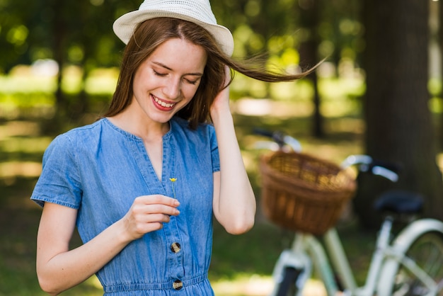 Donna del colpo medio che esamina un fiore Foto Gratuite