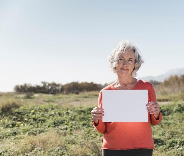 Donna del colpo medio che tiene un pezzo di carta Foto Gratuite
