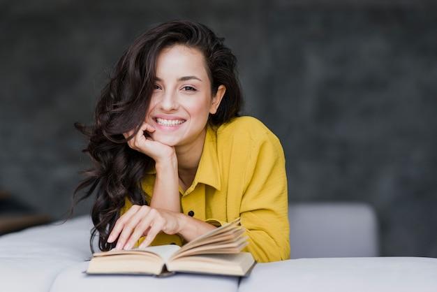 Donna del colpo medio con il libro che sorride alla macchina fotografica Foto Gratuite