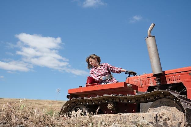 Donna del coltivatore che guida un trattore nel campo Foto Premium