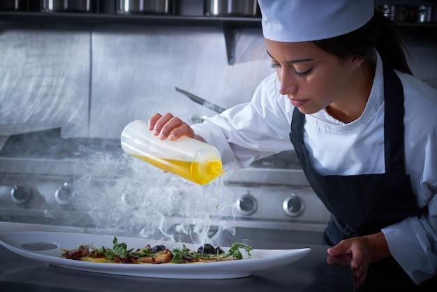 Donna del cuoco unico che lavora nella cucina con fumo Foto Premium