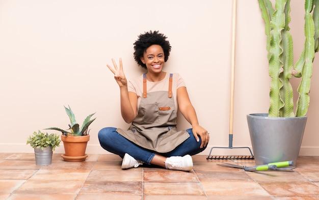 Donna del giardiniere che si siede sul pavimento Foto Premium