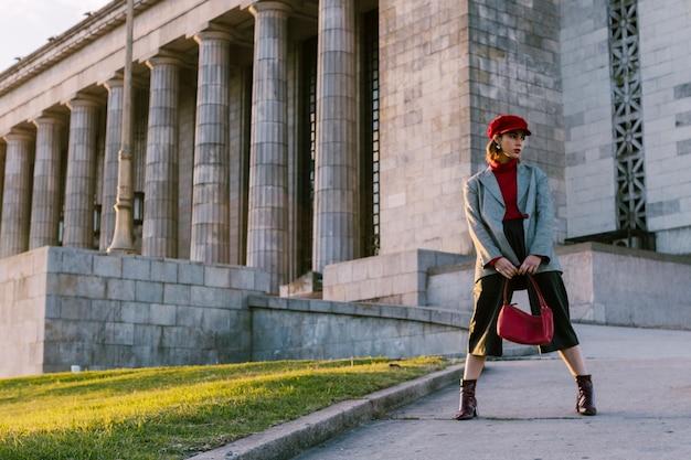 Donna del modello di moda di bellezza che indossa la borsa alla moda della tenuta del cappotto a disposizione Foto Gratuite