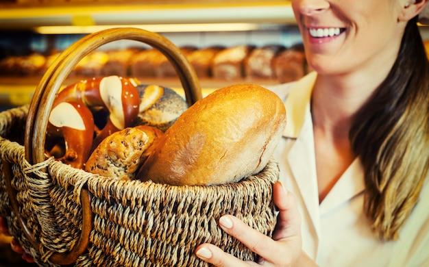 Donna del panettiere nel sostenitore che vende la merce nel carrello del pane Foto Premium