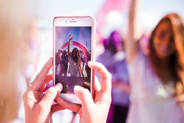 Donna del primo piano che cattura foto del suo amico sul telefono cellulare Foto Gratuite