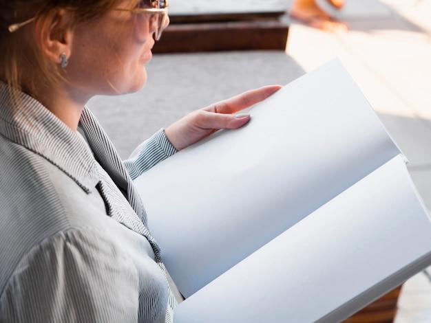 Donna del primo piano che legge una rivista del modello Foto Gratuite