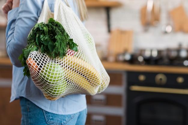 Donna del primo piano che porta borsa riutilizzabile con le drogherie organiche Foto Gratuite