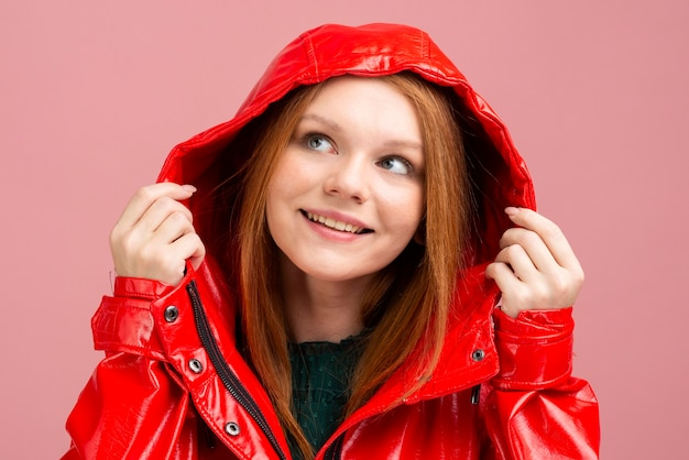 Donna del primo piano che porta la giacca di pioggia rossa Foto Gratuite