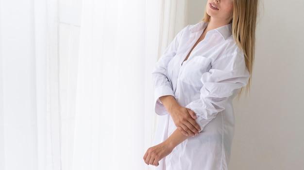 Donna del primo piano che posa in camicia bianca Foto Gratuite