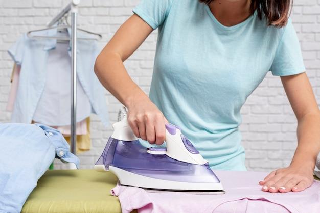Donna del primo piano che riveste di ferro una camicia Foto Gratuite