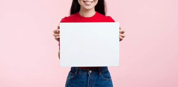 Donna del primo piano che tiene foglio di carta bianco Foto Gratuite
