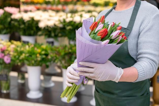 Donna del primo piano che tiene i tulipani eleganti Foto Gratuite