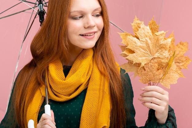 Donna del primo piano che tiene le foglie di giallo Foto Gratuite