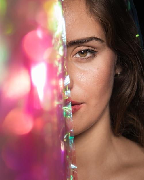 Donna del primo piano con gli occhi marroni e gli elementi sfocati Foto Gratuite