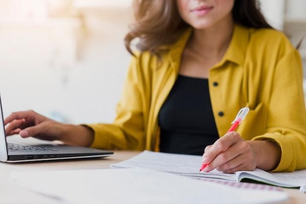 Donna del primo piano con scrittura del computer portatile Foto Gratuite