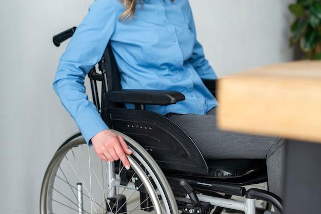 Donna del primo piano in sedia a rotelle all'ufficio Foto Gratuite