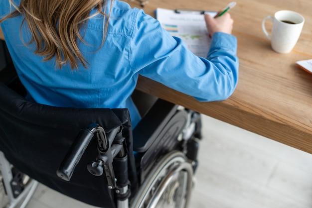 Donna del primo piano in sedia a rotelle che lavora all'ufficio Foto Gratuite