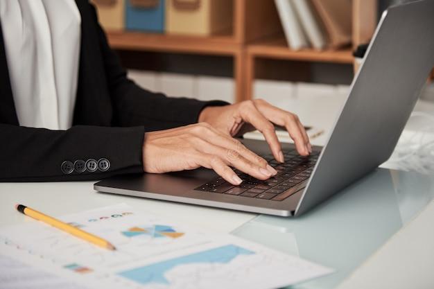 Donna del raccolto che scrive sul computer portatile Foto Gratuite