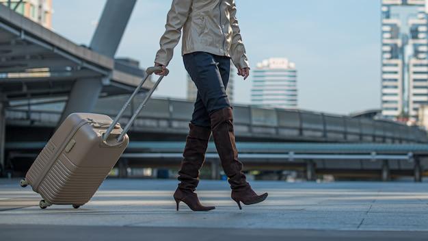 Donna del viaggiatore con la valigia che cammina nella città. Foto Premium