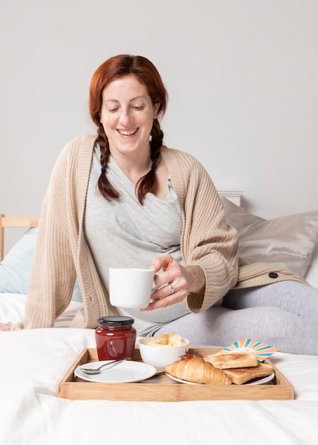 Donna dell'angolo alto che gode del brunch a letto Foto Gratuite