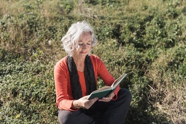 Donna dell'angolo alto che legge all'aperto Foto Gratuite
