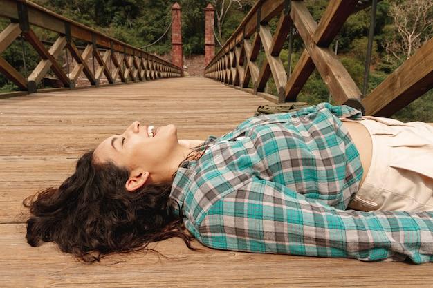 Donna dell'angolo alto posta sul ponte Foto Gratuite