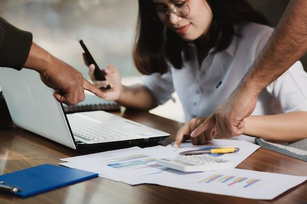 Donna dell'asia che usando felicemente smartphone, personal computer che lavora con gli amici. Foto Premium
