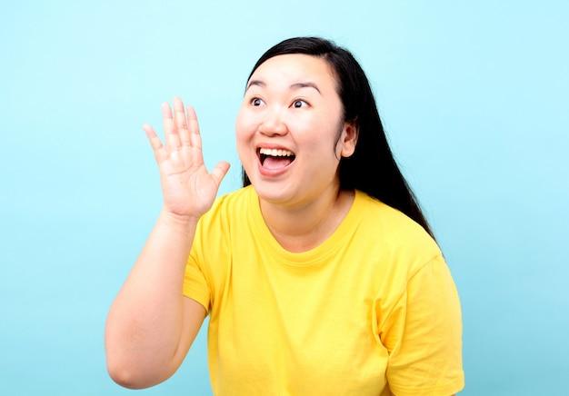 Donna dell'asia del ritratto che urla e mano sulla sua bocca, isolata su fondo blu in studio. Foto Premium