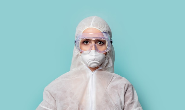 Donna dell'erba medica che indossa abbigliamento protettivo contro il virus su un fondo blu Foto Premium