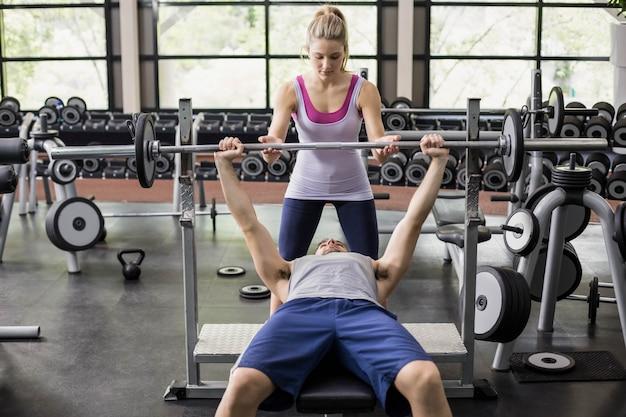 Donna dell'istruttore che aiuta uomo atletico in palestra Foto Premium