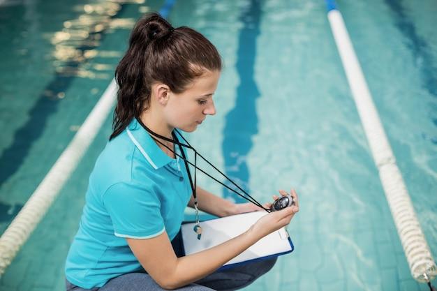 Donna dell'istruttore che tiene un cronometro sul poolside Foto Premium