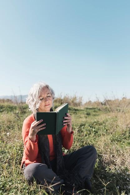 Donna della foto a figura intera che legge all'aperto Foto Gratuite
