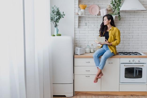 Donna della foto a figura intera con il libro nella cucina Foto Gratuite