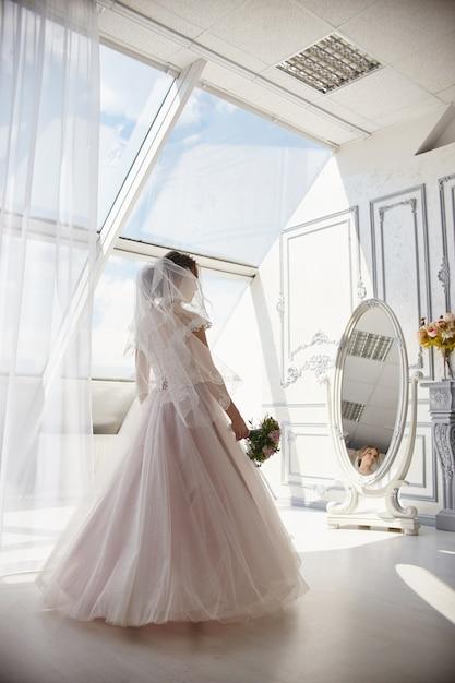 Donna della sposa di mattina nello sposo aspettante del vestito da sposa Foto Premium