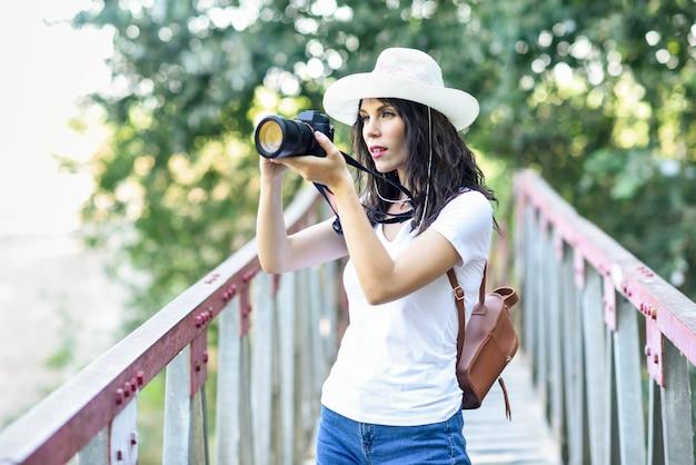 Donna della viandante che prende le fotografie con una macchina fotografica mirrorless Foto Premium